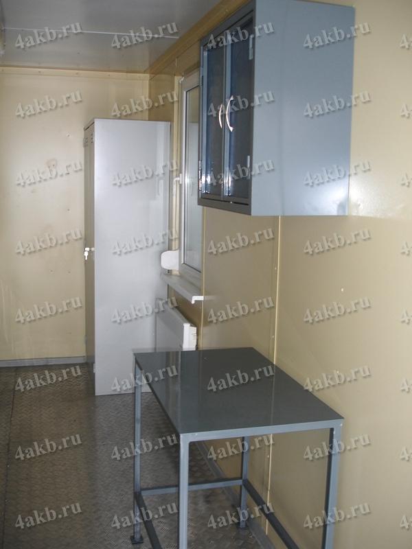 Металлический шкаф и стол в мобильной аккумуляторной мастерской
